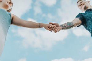dwie osoby trzymają się za rękę podczas randki